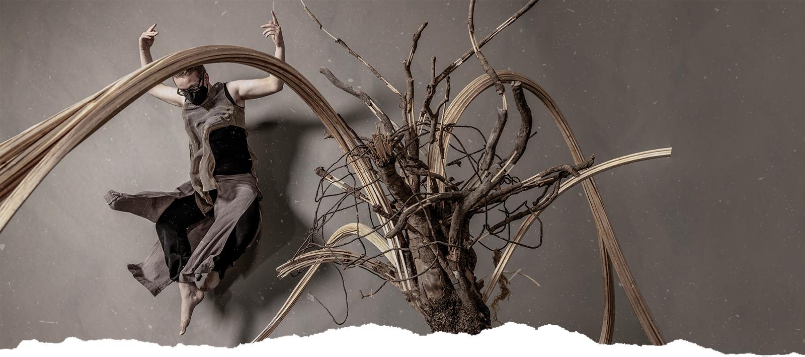 A dancer jumps next to a sculpture