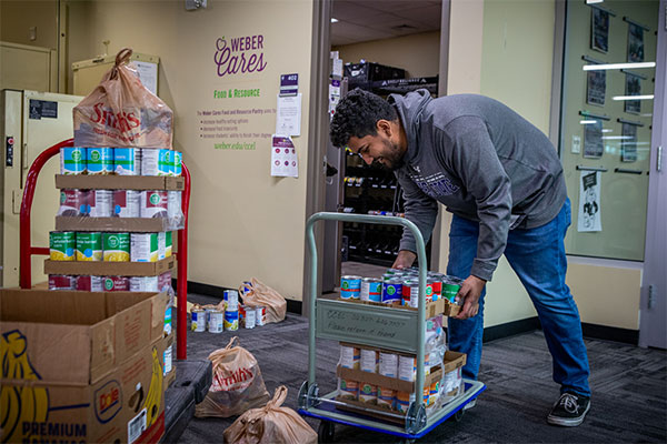 student adding food to pantry