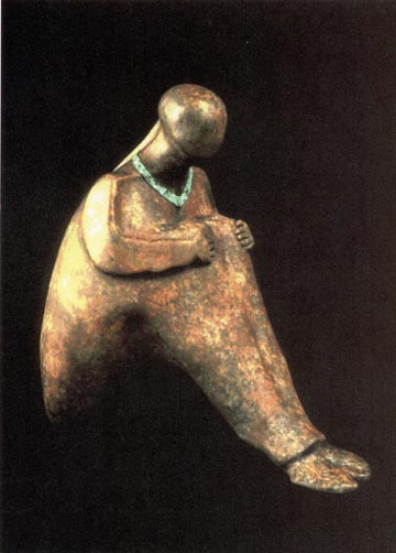 Color picture of bronze statue of a woman sitting on the ground.