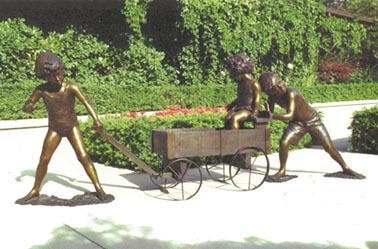 Bronze sculpture depicting children pushing and pulling a wagon with another child inside.