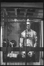 picture of tatooed man behind bars, another lifting weights in the background.