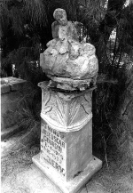 A photo of a tombstone with an angel sitting on top.